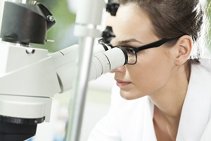 Picture of scientist looking through a microscope